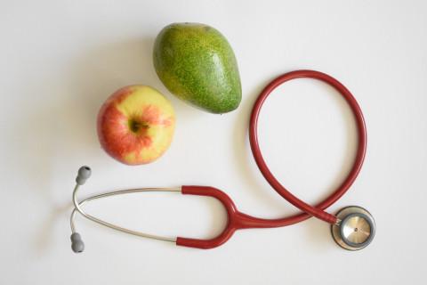 Frutas y estetoscopio que simbolizan estudiar dietética