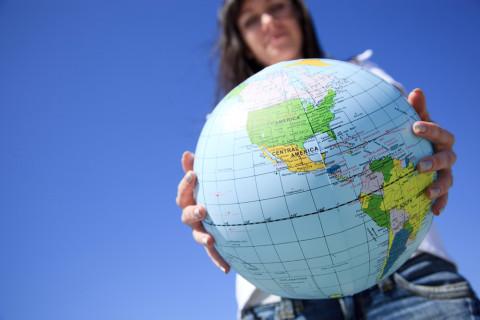 Estudiante de ecoturismo con un globo terráqueo en las manos