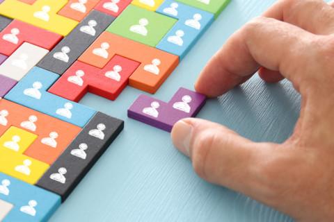Hombre colocando una pieza de puzzle con símbolos de personas