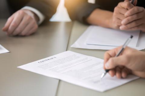 Chico firmando un contrato tras hacer un Máster en Dirección y Gestión Laboral