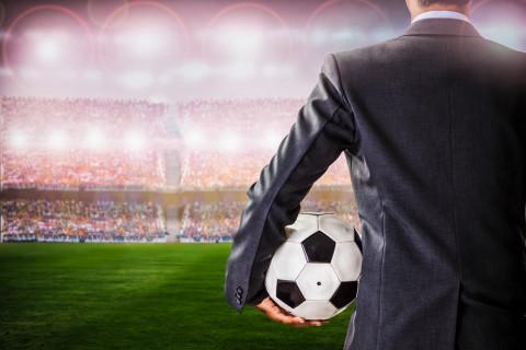 Hombre de traje en un estadio con un balón