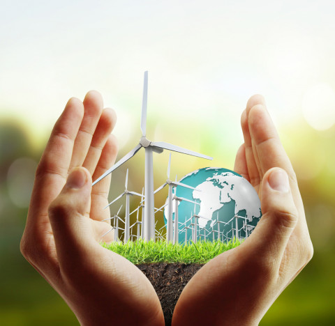Manos con un planeta verde representando máster en energías renovables y proyectos energéticos