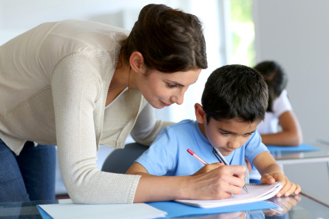 Profesora con un master en educación y docencia enseñando a unalumno