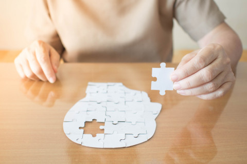 Mujer haciendo un puzzle como terapia de psicología transpersonal