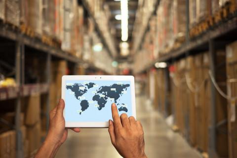 Trabajador con una tablet en un almacén de logística y transporte internacional
